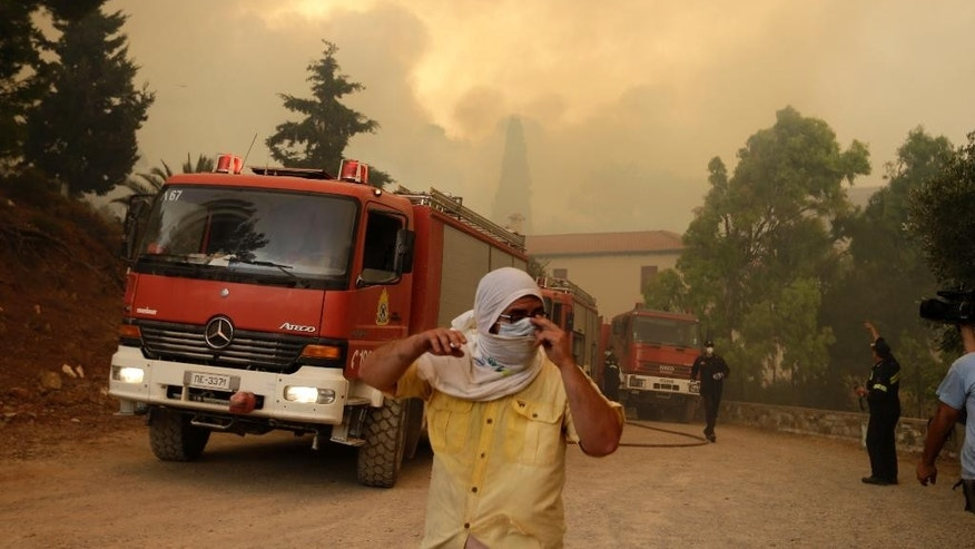 Local residents and firefighters try to save Galataki Monastery as a fire approaches the area near the seaside village of Limni on the island of Evia, about 160kilometers (100 miles) north of Athens on Monday, Aug. 1, 2016. Nearly 200 firemen, assisted by water-dropping aircraft, fire engines and volunteers, are fighting a large forest fire that has raged through the Greek island of Evia for the past three days. (AP Photo/Thanassis Stavrakis)