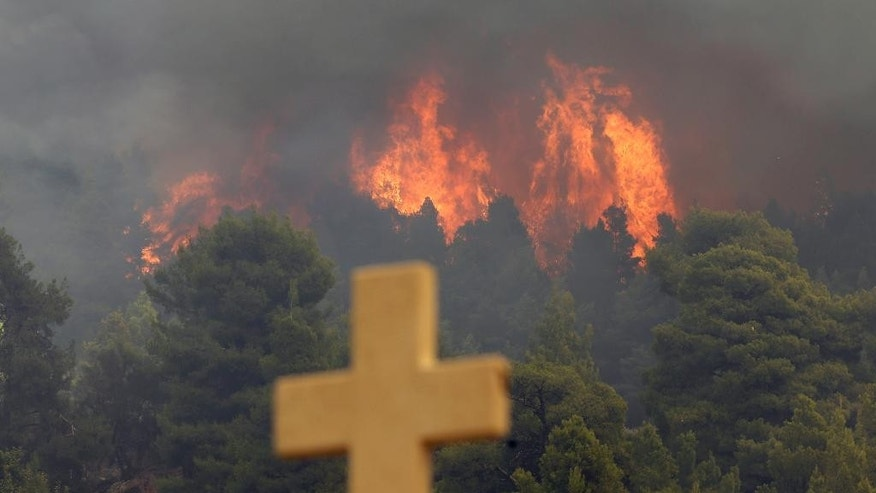 A fire burns over the Galataki Monastery near the village of Limni on the island of Evia, about 160kilometers (100 miles) north of Athens on Monday, Aug. 1, 2016. Nearly 200 firemen, assisted by water-dropping aircraft, fire engines and volunteers, are fighting a large forest fire that has raged through the Greek island of Evia for the past three days. (AP Photo/Thanassis Stavrakis)