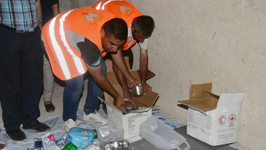 In this photo released on Friday, July 29, 2016 by the Syrian official news agency SANA, municipal workers prepare aid inside buildings prepared by the Syrian government to host people who will left rebel-held neighborhoods of the northern city of Aleppo, Syria. Syrian state media is reporting that dozens of families have started leaving besieged rebel-held neighborhoods in the northern city of Aleppo after the government opened safe corridors for civilians and fighters who want to leave. The Russian military says 169 civilians have left through the corridors since they were set up, but Syrian opposition activists say no civilians have left besieged parts of the city. (SANA via AP)