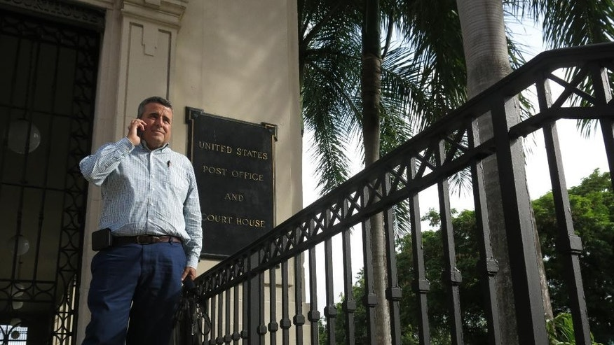 In this July 26, 2016 photo, attorney Santiago Mari talks to a client in front of a federal courthouse in San Juan, Puerto Rico. He is one of tens of thousands of Puerto Rico bond holders who see a glimmer of hope in a new restructuring plan recently approved by the U.S. government that could help recover some of their losses. (AP Photo/Danica Coto)