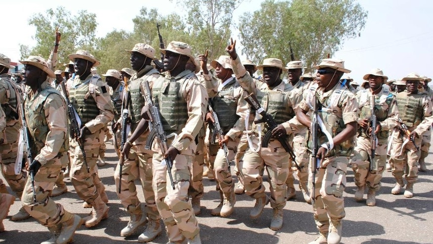 FILE- In this Thursday, Jan. 17, 2013 file photo, Nigeria battalion 1 troops, part of the African led international support mission to Mali sing before their departure, at the peace keeping centre in Jaji, Kaduna, Nigeria. Nigeria's army gunned down 348 Shiites in an attack in which one soldier was killed, according to the report of a commission of inquiry published Monday, Aug. 1, 2016 which calls for all those involved in the killings to be prosecuted. (AP Photo file)