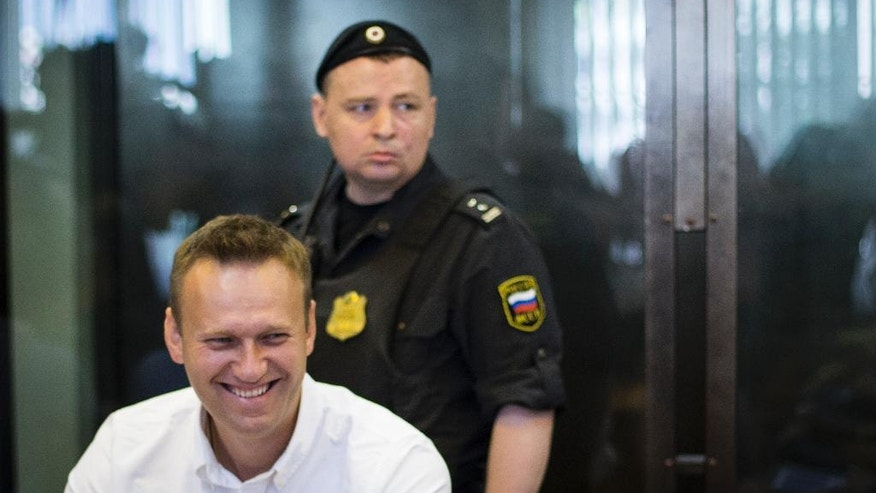 Russian opposition activist Alexei Navalny , foreground, smiles as he sits in a courtroom in Moscow on Monday, Aug. 1, 2016. Russian court did not approve prosecutor's appeal to change Alexei Navalny's suspended sentence into a jail term. (AP Photo/Ivan Sekretarev)