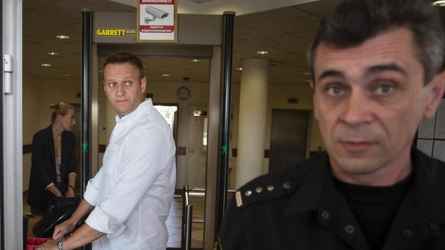 Russian opposition activist Alexei Navalny, center, undergoes security check at an entrance to a courtroom in Moscow on Monday, Aug. 1, 2016. Russian court did not approve prosecutor's appeal to change Alexei Navalny's suspended sentence into a jail term. (AP Photo/Ivan Sekretarev)