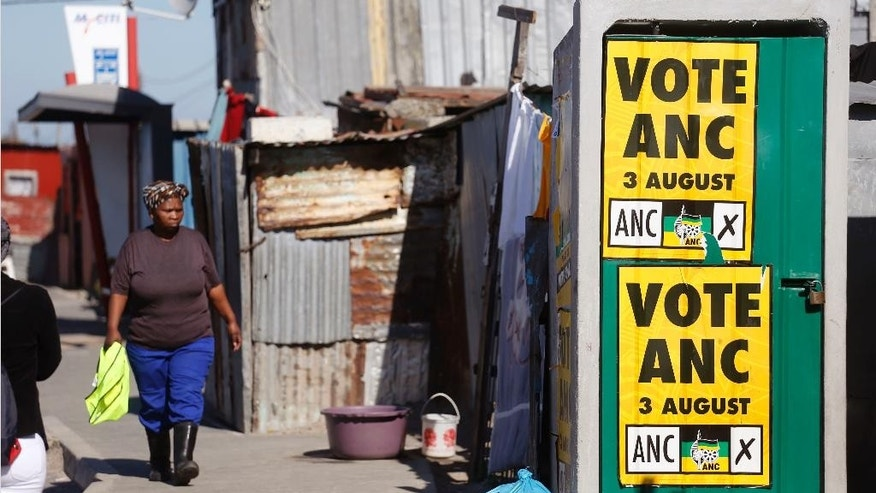 A woman, left, walks near an African National Congress, ANC, political poster fixed on a toilet door, that call South Africans to vote during municipal elections in the township of Khayelitsha on the outskirts of Cape Town, South Africa, Tuesday, Aug. 1, 2016. South Africa's ruling party faces a robust challenge in municipal elections on Wednesday from opposition groups seeking to capitalize on scandals linked to President Jacob Zuma. (AP Photo/Schalk van Zuydam)