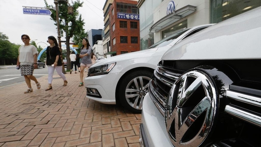 The Volkswagen emblem is seen on a vehicle in front of a dealership in Seoul, South Korea, Tuesday, Aug. 2, 2016. South Korea has fined Volkswagen 17.8 billion won ($16 million) and suspended sales of 80 VW models, alleging the German carmaker fabricated documents on emissions or noise level tests. (AP Photo/Ahn Young-joon)