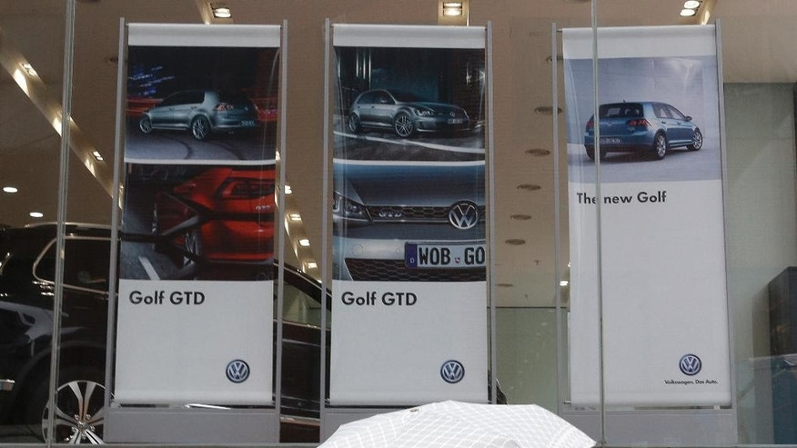 Women pass by banners advertising Volkswagen's Golf at a dealership in Seoul, South Korea, Tuesday, Aug. 2, 2016. South Korea has fined Volkswagen 17.8 billion won ($16 million) and suspended sales of 80 VW models, alleging the German carmaker fabricated documents on emissions or noise level tests. (AP Photo/Ahn Young-joon)