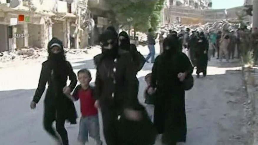 This still image from Syrian state TV video, shows women and children arriving in a street lined with heavily damaged buildings in the government-held part of the Salaheddine neighborhood of Aleppo, Syria, Saturday, July 30, 2016, Syrian state media is reporting that dozens of families have started leaving besieged rebel-held neighborhoods in the northern city of Aleppo after the government opened safe corridors for civilians and fighters who want to leave. The Russian military says 169 civilians have left through the corridors since they were set up, but Syrian opposition activists say no civilians have left besieged parts of the city. (Syrian State TV, via AP)
