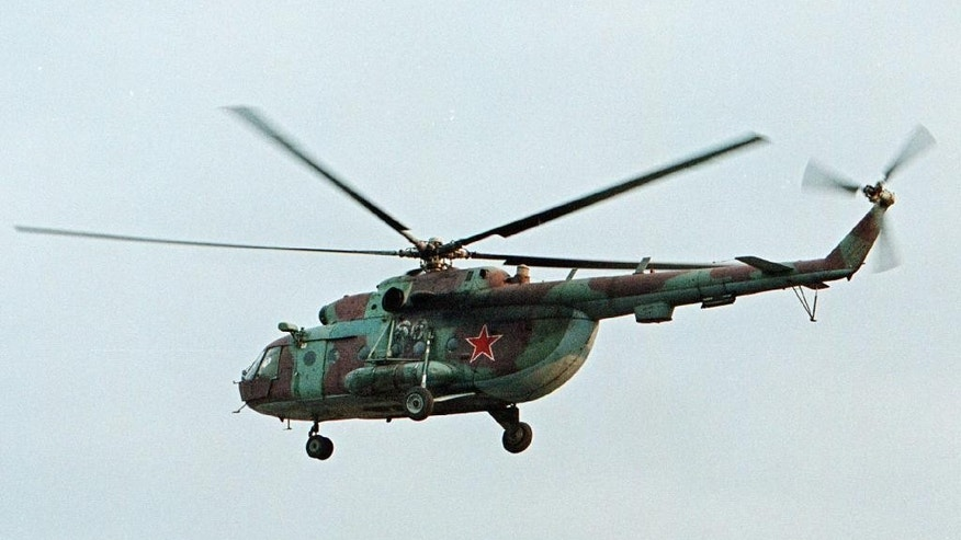 FILE In this in this Sept. 18, 2002 file photo a Mi-8 helicopter flies over the Chechen regional capital Grozny, Russia. A helicopter similar to the one pictured has been shot down in Syria and Russian President Vladimir Putin's spokesman says all people aboard it have been killed, Monday, Aug. 1, 2016. (AP Photo/Musa Sadulayev, File)