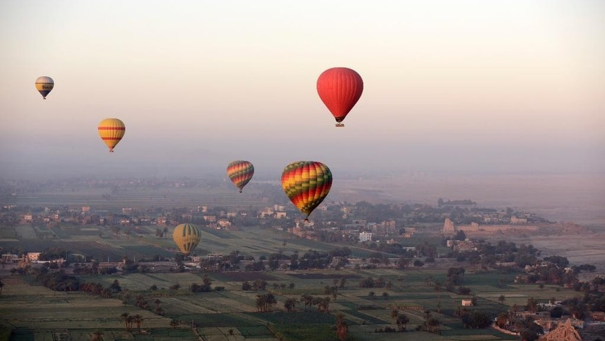 FILE -- In this April 1, 2016 file photo taken from a balloon, hot air balloons fly over the west bank of the Nile River in Luxor, Egypt.  The weekend's hot balloon crash in Texas has been a grim reminder of a similar but deadlier accident in Egypt three years ago, when 18 foreign tourists burnt to death before plummeting to earth as their sightseeing sunrise flight over the famed temples of the ancient city of Luxor drew to a close.(AP Photo/Amr Nabil, File)