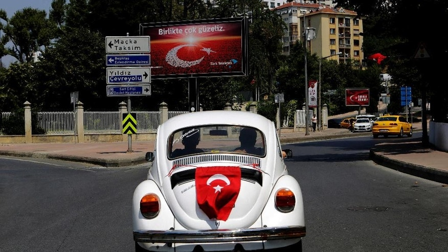 Two men drive in a German made Volkswagen Beetle with a Turkey on the back, in Istanbul, on Monday, Aug. 1, 2016. Turkey slammed a German court decision that prevented President Recep Tayyip Erdogan from addressing a demonstration in Germany denouncing Turkey's failed July 15 coup, and summoned a German diplomat in protest. (AP Photo/Petros Karadjias)
