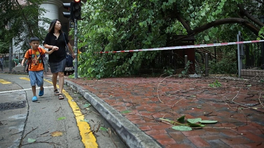 People walk past tree branches broken by strong winds caused by Typhoon Nida in Hong Kong, Tuesday, Aug. 2, 2016. The Hong Kong Observatory issued the number 8 storm signal as Typhoon Nida moves northwest across southern China, bringing high winds and heavy rain but no immediate reports of deaths or destruction. (AP Photo/Kin Cheung)