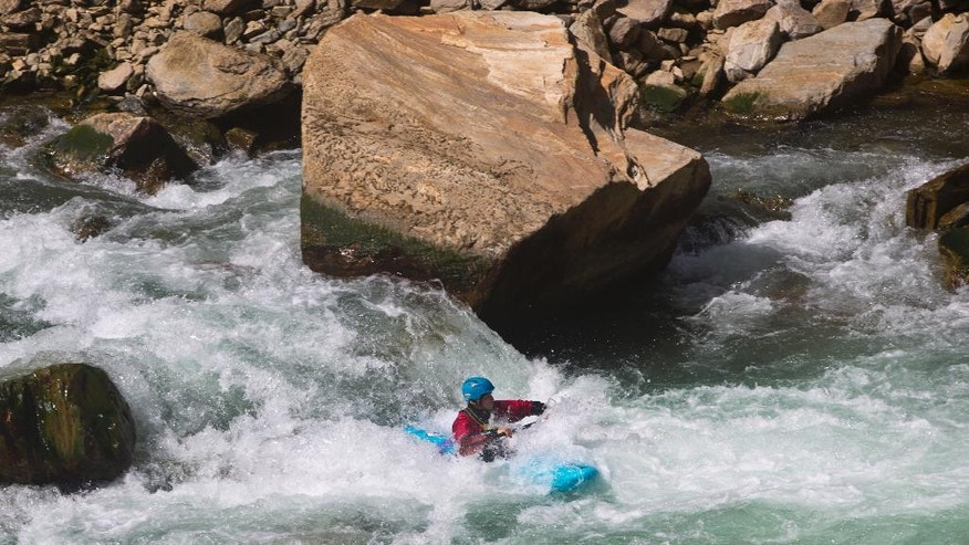 In this July 17, 2016 photo, Austrian tourist, Kristof Stursa, kayaks along the Panjshir River, in Panjshir province, north of the capital, Kabul, Afghanistan. On a recent sunny morning in northern Afghanistan, excited children and bemused policemen lined the banks of the fast-flowing river to watch a group of Europeans navigate the white water in multi-colored kayaks. A group of keen amateur kayakers have travelled to Panjshir province to test the white water and introduce the local community to the sport -- and they hope others will soon follow them. (AP Photos/Massoud Hossaini)