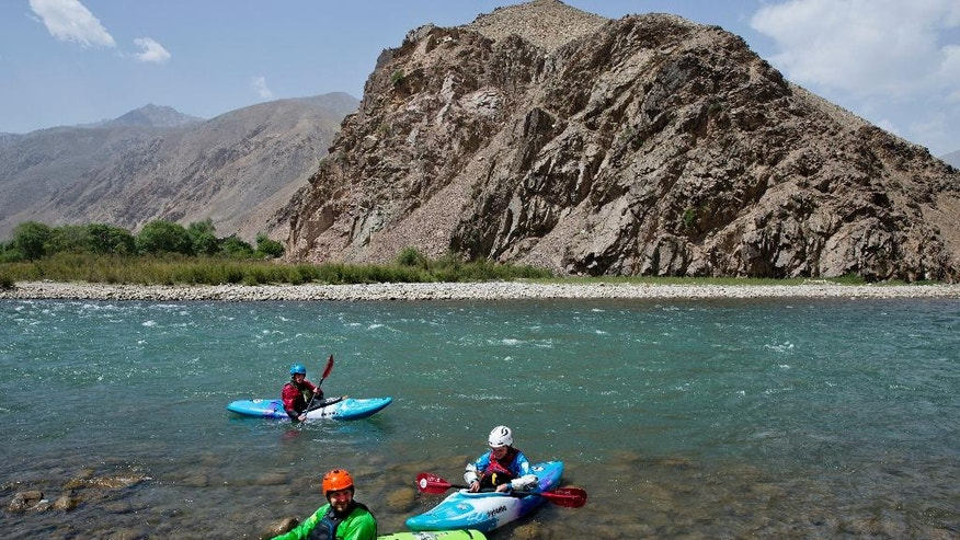 In this Sunday, July 17, 2016 photo, three foreign tourists kayak along the Panjshir River in Panjshir province, north of capital Kabul, Afghanistan. In Excited children and bemused police lined the banks of the fast-flowing river on a recent sunny morning to watch a group of Europeans in brightly colored kayaks navigate the white water as a drone-mounted camera followed their progress like a manic mosquito. (AP Photos/Massoud Hossaini)