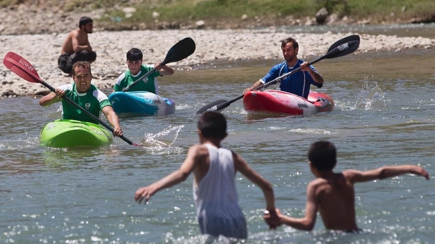 In this Tuesday, July 19, 2016 photo, Afghan trainees practice kayaking along the Panjshir River in Panjshir province, north of capital Kabul, Afghanistan. In Afghanistan's Panjshir province, excited children and bemused police lined the banks of the fast-flowing river on a recent sunny morning to watch a group of Europeans in brightly colored kayaks navigate the white water as a drone-mounted camera followed their progress like a manic mosquito. (AP Photos/Massoud Hossaini)