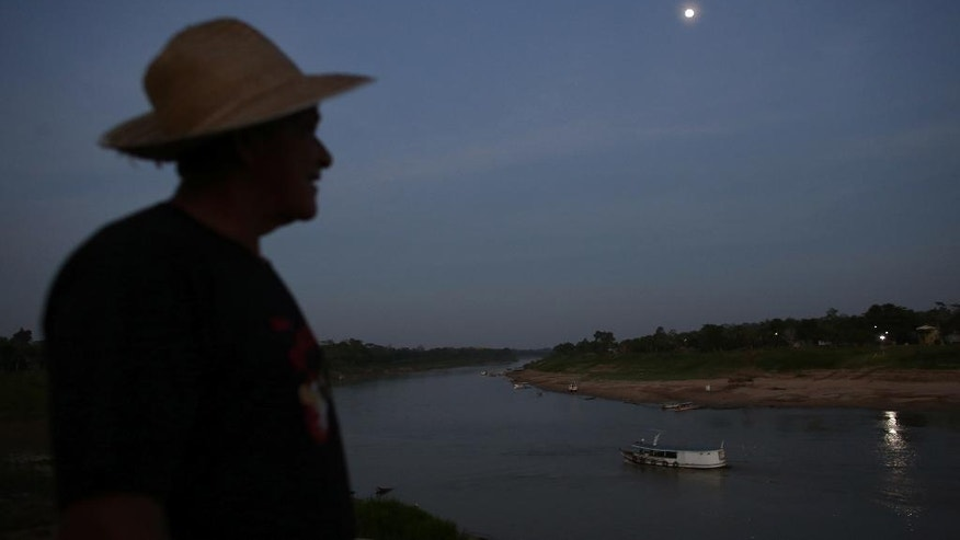 In this June 22, 2016 photo, a boatman gets ready to cross the Purus river near the city of Boca do Acre, Amazonas state, Brazil. The Purus river provides the main access to the community of Ceu do Mapia in a trip of more than four hours deep in the Amazon jungle of western Brazil. (AP Photo/Eraldo Peres)
