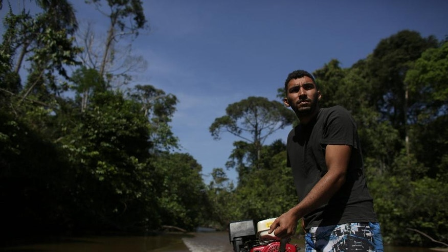 In this June 22, 2016 photo, boatman Sebastiao Melo pilots his boat through the Igarape Mapia river towards the Ceu do Mapia community in Amazonas state, Brazil. This community revolves around an ancient psychedelic tea locals know as the Holy Daime. The Ayahuasca brew is sacred to Ceu do Mapia villagers, who use it in rituals that blend together Indian beliefs with Roman Catholicism. (AP Photo/Eraldo Peres)