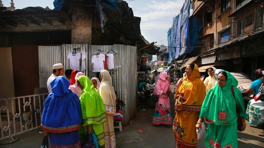 In this Feb. 21, 2016 photo, Indian Dawoodi Bohra women walk past others shopping for clothes in a Bohra neighborhood in Mumbai, India. The Dawoodi Bohras are an affluent trading community of about a million people concentrated mostly in Mumbai, but also seen across the United States and Europe. The community has a longstanding tradition of circumcising girls, known as khatna, going back to their roots in Yemen and its proximity to northern and northeastern Africa, where the practice is deeply entrenched. (AP Photo/Rafiq Maqbool)