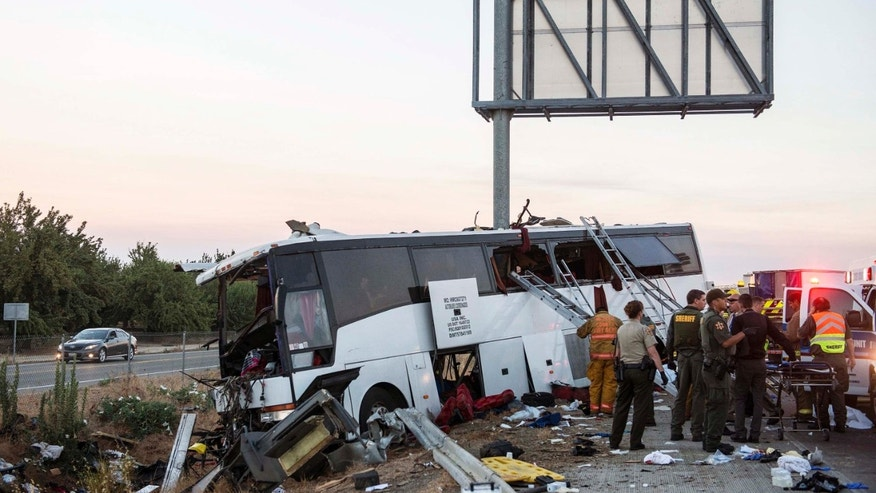 Rescue crews work at the scene of a charter bus crash on northbound Highway 99 between Atwater and Livingston, Calif., Tuesday, Aug. 2, 2016. A charter bus veered off a central California freeway before dawn Tuesday and struck a pole that sliced the vehicle nearly in half. (Andrew Kuhn/Merced Sun-Star via AP)