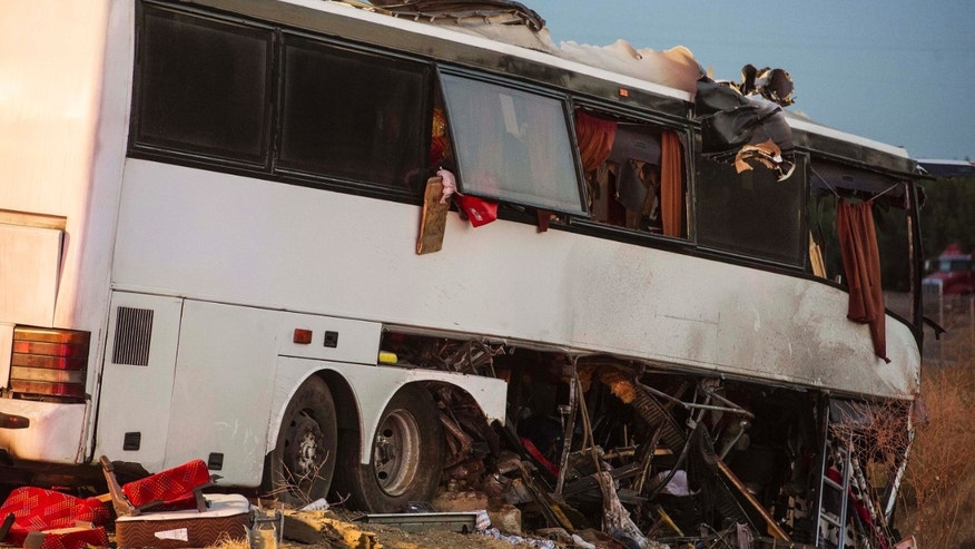The wreckage of a charter bus sits on northbound Highway 99 between Atwater and Livingston, Calif., Tuesday, Aug. 2, 2016. The bus veered off the central California freeway before dawn Tuesday and struck a pole that sliced the vehicle nearly in half, authorities said. (Andrew Kuhn/Merced Sun-Star via AP)