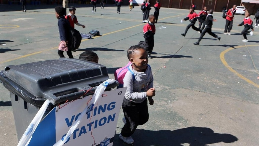 Children leave their school which is being used as polling station, on the eve of the country's municipal elections in Johannesburg, Tuesday, Aug. 2, 2016. This election season has been deadly for candidates and party activists in South Africa, with more than 12 killed ahead of Wednesday's vote. National police have determined it a serious enough problem to create a task force to investigate the deaths, most occurring in KwaZulu-Natal province. (AP Photo/Denis Farrell)