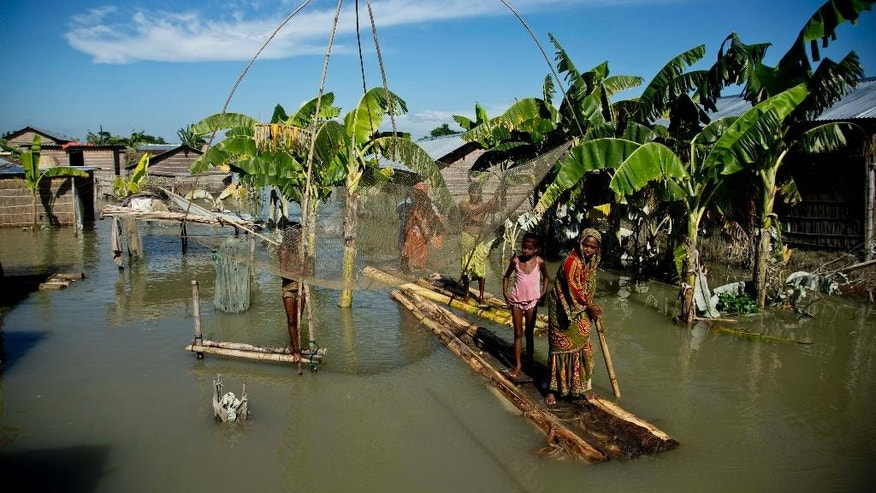 FILE - In this Sunday, July 31, 2016, file photo, a flood affected family moves on a banana raft past a fishing net in Morigaon district, east of Gauhati, northeastern Assam state, India. Incessant downpours have damaged swaths of land, uprooted trees and snapped telephone cables in dozens of districts in the states of Bihar in the east, Assam in the remote northeast and Himachal Pradesh in the north. (AP Photo/Anupam Nath, File)
