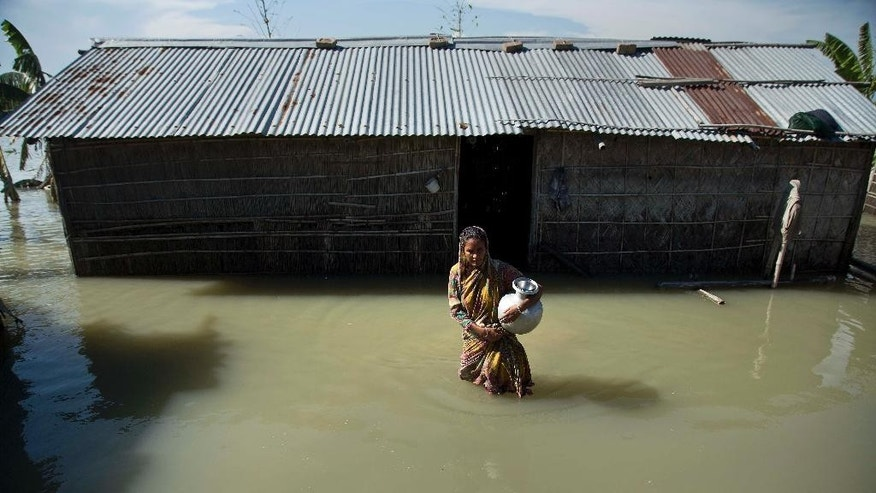 FILE- In this July 31, 2016, file photo, a flood affected woman wades through water near her partially submerged house in Morigaon district, east of Gauhati, northeastern Assam state, India. Incessant downpours have damaged swaths of land, uprooted trees and snapped telephone cables in dozens of districts in the states of Bihar in the east, Assam in the remote northeast and Himachal Pradesh in the north. (AP Photo/Anupam Nath, File)WLD