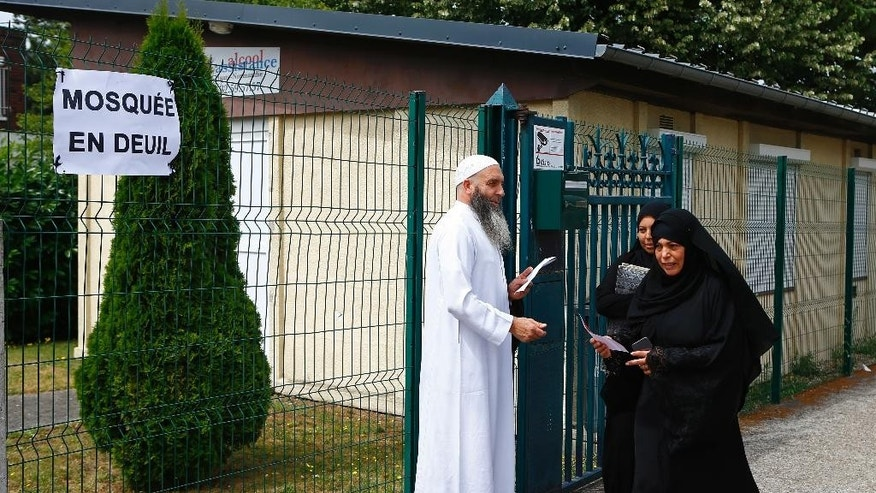 "Muslim worshippers walk past a poster reading ""Mourning Mosque"" after the friday prayer at the Yahya Mosque, in Saint-Etienne-du-Rouvray, Normandy, France, Friday, July 29, 2016. Four days after the hostage taking in Saint-Etienne-du-Rouvray, officials and worshippers of the muslim community paid tribute to Priest Jacques Hamel and Christian community. (AP Photo/Francois Mori)"