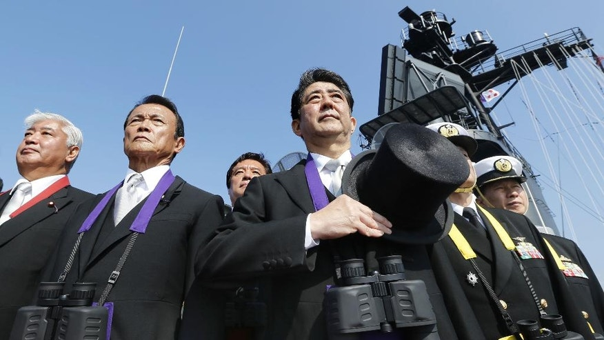 "FILE - In this Oct. 18, 2015 file photo, Japanese Prime Minister Shinzo Abe, center, stands with Deputy Prime Minister and Finance Minister Taro Aso, second left, and Defense Minister Gen Nakatani, left, during the official triennial Maritime Self-Defense Force fleet review aboard the JMSDF escort ship Kurama in the waters off Sagami Bay, south of Tokyo.  Japan has called North Korea's nuclear and missile development a ""grave and imminent threat"" to the region and international security, and criticized China's increasingly assertive military action in its annual defense report.  The report, approved Tuesday, Aug. 2, 2016,  by the Cabinet, comes as Prime Minister Shinzo Abe's government pushes for Japan to take on greater military roles abroad.   (Kazuhiko Yamashita/Kyodo News via AP, File)"