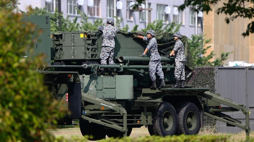 "FILE - In this June 21, 2016 file photo, Japan Self-Defense Force members set up a PAC-3 Patriot missile unit deployed in case of a North Korean rocket launch at the Defense Ministry in Tokyo.  Japan has called North Korea's nuclear and missile development a ""grave and imminent threat"" to the region and international security, and criticized China's increasingly assertive military action in its annual defense report.  The report, approved Tuesday, Aug. 2, 2016,  by the Cabinet, comes as Prime Minister Shinzo Abe's government pushes for Japan to take on greater military roles abroad.  (AP Photo/Shizuo Kambayashi, File)"