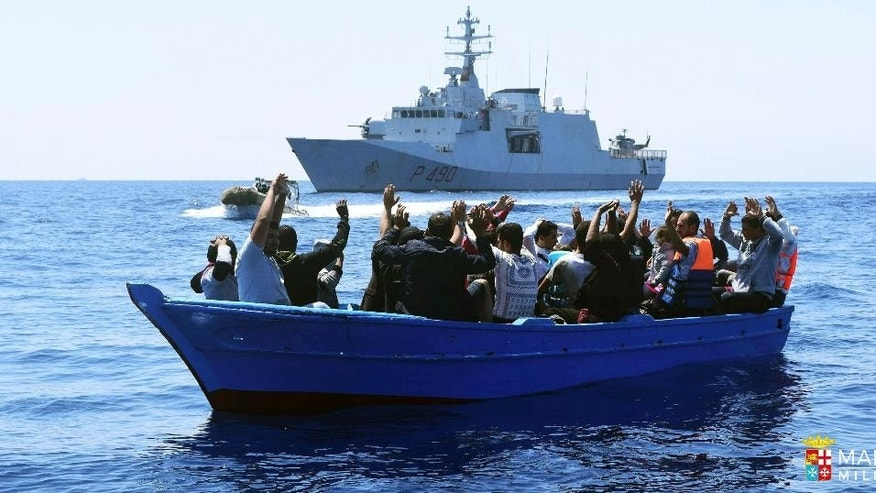Migrants raise their arms as they are rescued at sea by the Italian Navy Marina Militare Fulgosi vessel in this image made available Tuesday, Aug. 2, 2016. According to the Italian Navy, three Italian Navy boats rescued over 560 people in the southern Mediterranean Sea on Monday, Aug. 1, 2016. Hundreds of thousands of migrants arrive in smugglers' boats on Europe's southern shores. (Marina Militare Italian Navy via AP)