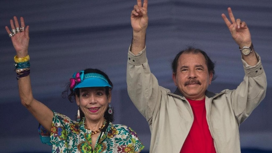 FILE - In this July 3, 2015, file photo, Nicaragua's President Daniel Ortega, right, and first lady Rosario Murillo, wave to supporters during an event commemorating the 36th anniversary of the Sandinista National Liberation Front withdrawal to Masaya, in Managua, Nicaragua. Nicaragua's governing Sandinista party has named the first lady on Tuesday, Aug. 2, 2016, as the running-mate of President Ortega in his bid for a third term in Nov. 6 election. (AP Photo/Esteban Felix,File)