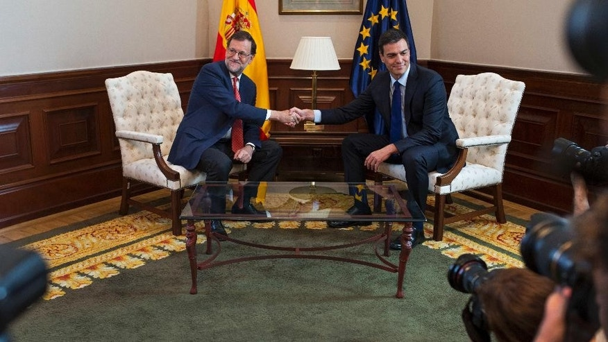 Spain's acting Prime Minister Mariano Rajoy, left, shakes hands with Socialists Party leader Pedro Sanchez as they poses for the media before their meeting at the Spanish parliament in Madrid, Spain, Tuesday, Aug. 2, 2016. (AP Photo/Francisco Seco)