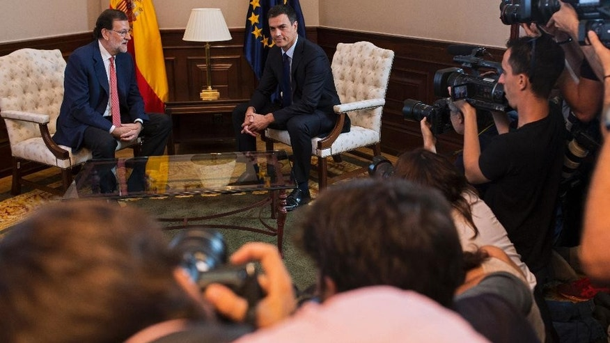 Spain's acting Prime Minister Mariano Rajoy, left, talks to Socialists Party leader Pedro Sanchez as they pose for the media before their meeting at the Spanish parliament in Madrid, Spain, Tuesday, Aug. 2, 2016. (AP Photo/Francisco Seco)