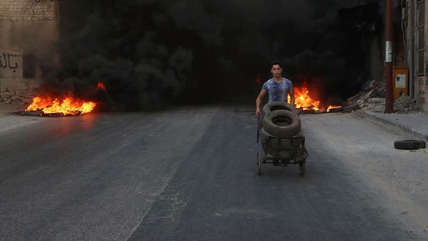 This Sunday, July. 31, 2016 photo, provided by the Syrian anti-government activist group Aleppo Media Center (AMC), shows a Syrian young man burns tyres in an attempt to prevent airstrikes above Aleppo, Syria. Residents trapped in rebel-controlled Aleppo are struggling to survive the crippling encirclement of their once thriving city. Bread, medication and fuel are running short. For the tens of thousands who chose to remain, the battle for Aleppo is a pivot point in the Syrian war. (Aleppo Media Center via AP)