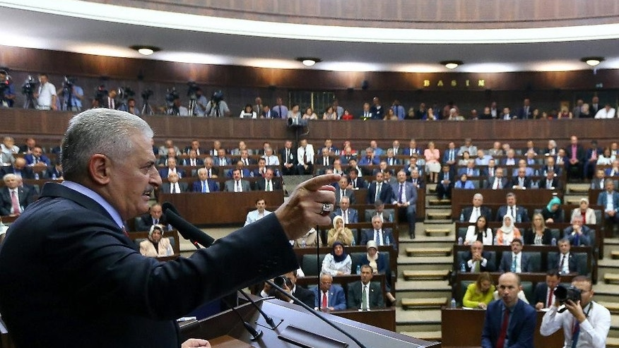 Turkey's Prime Minister Binali Yildirim, left, addresses in the Parliament in Ankara, Turkey, on Tuesday, Aug. 2, 2016. Yildirim announced plans Tuesday to shut down two military high courts _ the administrative and appeals, and said military courts, which deal with disciplinary issues, would be placed under the Defense Ministry's supervision (Hakan Goktepe/Pool Photo via AP)
