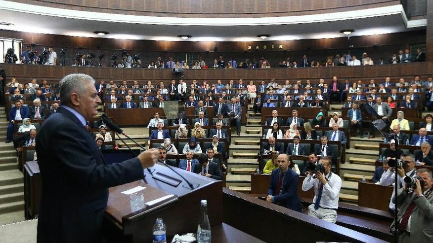 Turkey's Prime Minister Binali Yildirim, left, addresses in the Parliament in Ankara, Turkey, on Tuesday, Aug. 2, 2016. Yildirim announced plans Tuesday to shut down two military high courts the administrative and appeals, and said military courts, which deal with disciplinary issues, would be placed under the Defense Ministry's supervision (Hakan Goktepe/Pool Photo via AP)