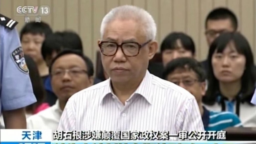 In this image from video released on Wednesday, Aug. 3, 2016 by China's CCTV and made available via AP Video, Chinese legal rights activist Hu Shigen stands for his trial at the Tianjin No. 2 Intermediate People's Court in northern China's Tianjin Municipality. Hu was sentenced to 7 ½ years in prison on subversion charges Wednesday, in the second in a series of cases underscoring the ruling Communist Party's determination to rein in government critics. (CCTV via AP Video)