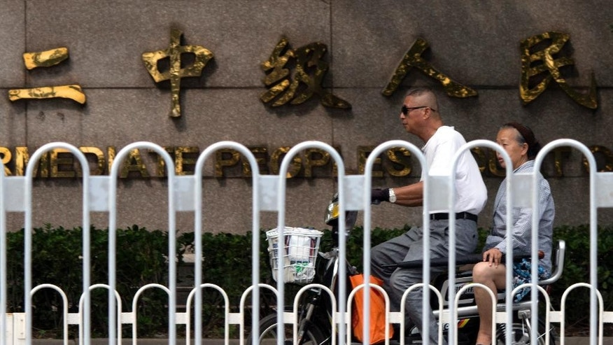 In this photo taken Tuesday, Aug. 2, 2016, an elderly man and woman ride on an electric bike past the Chinese words for Tianjin No. 2 Intermediate People's Court in northern China's Tianjin Municipality. The official Xinhua News Agency reported Wednesday, Aug. 3, 2016 that Chinese legal activist Hu Shigen has gone on trial on subversion charges at the Tianjin court in the second in a series of cases underscoring the ruling Communist Party's determination to reign in government critics.(AP Photo/Ng Han Guan)