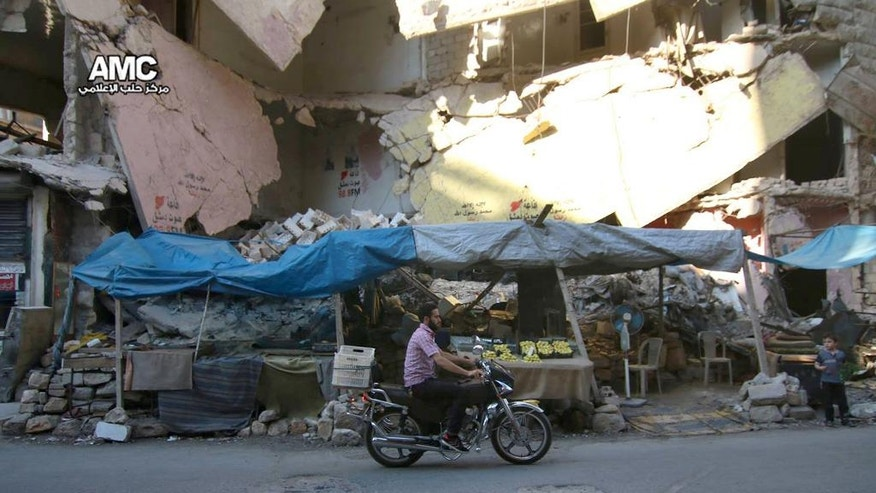 In this Friday, July. 29, 2016 photo, provided by the Syrian anti-government activist group Aleppo Media Center (AMC), shows a Syrian man rides a motorcycle passes by a damaged building that was destroyed by airstrikes in Aleppo, Syria. Residents trapped in rebel-controlled Aleppo are struggling to survive the crippling encirclement of their once thriving city. Bread, medication and fuel are running short. For the tens of thousands who chose to remain, the battle for Aleppo is a pivot point in the Syrian war. (Aleppo Media Center via AP)