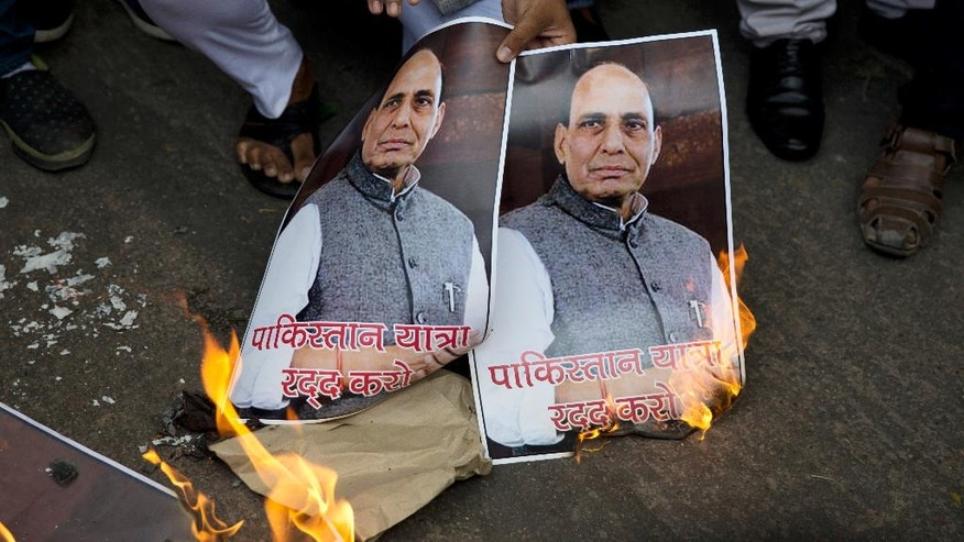 An activist of Hindu Sena or Hindu Army burns photographs of Indian Home Minister Rajnath Singh, during a protest against Singh's upcoming visit to Pakistan, in New Delhi, India, Tuesday, Aug. 2, 2016. The protesters, who propagate an extremely ultra Hindu nationalist view, demand that India cut off all ties with Pakistan. (AP Photo/Tsering Topgyal)