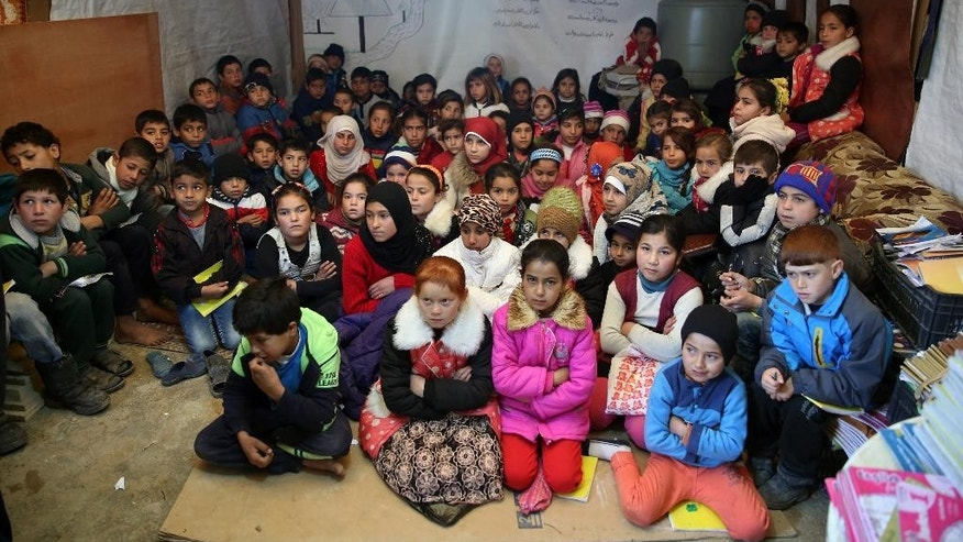 FILE - In this Wednesday, Jan. 27, 2016 file photo, Syrian refugee children sit on the ground as they listen to their teacher inside a tent, home for a refugee family that has been turned into a makeshift school, in a Syrian refugee camp in the eastern town of Kab Elias, Lebanon. School budgets in the Middle East are facing major shortfalls in the run up to the new academic year, leaving some one million Syrian refugee children out of schools, according to a new report by the international children's charity Their World. (AP Photo/Bilal Hussein, File)