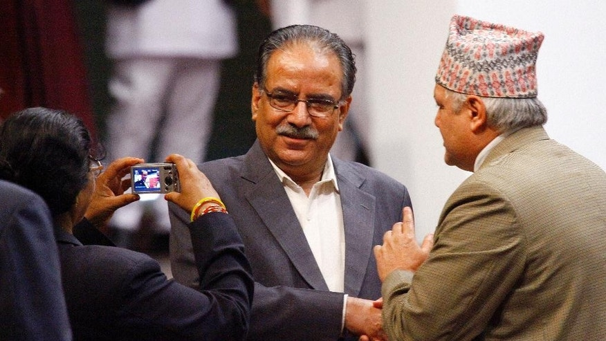 A Nepalese lawmaker, left, takes photographs of newly-appointed prime minister Pushpa Kamal Dahal, center, in Kathmandu, Nepal, Wednesday, Aug.3, 2016. Nepal's parliament elected the former communist rebel leader as the country's new prime minister Wednesday who would now lead a coalition government and likely give continuation to political instability in the Himalayan nation.(AP Photo/Bikram Rai)