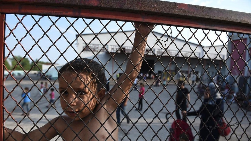 FILE - In this photo taken on Saturday, June 25, 2016 a child stands behind a fence during a protest against the living conditions at the Oreokastro camp, near the northern town of Thessaloniki, Greece. A government official in Athens on Wednesday, Aug. 3, 2106 said to the Associated Press that there is no sign yet that a deal between the European Union and Turkey to stop migrants coming to Europe has faltered since the attempted military coup in the country. (AP Photo/Giannis Papanikos, File)