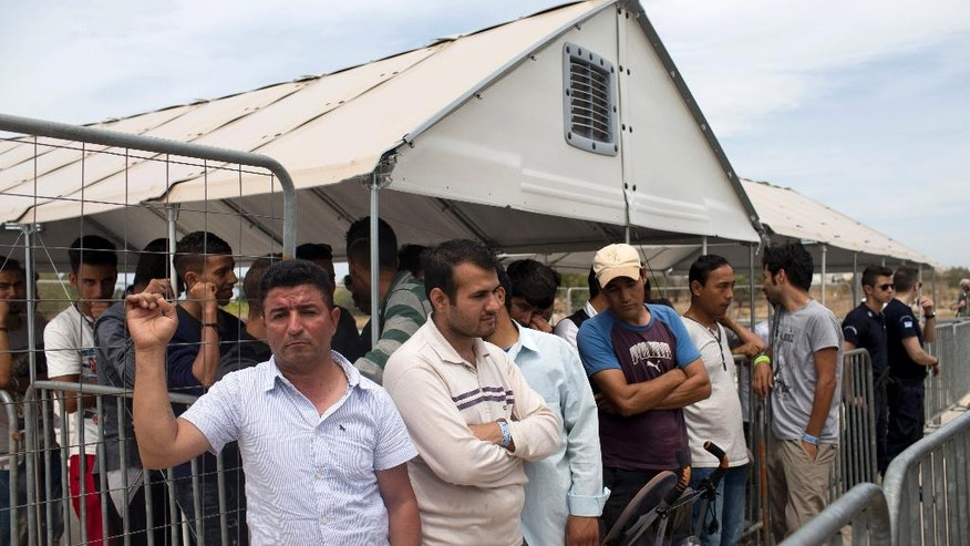FILE - In this file photo taken on Monday, June 13, 2016, migrants who live in the Hellenikon refugee and migrant camp in  Athens wait to register for asylum. A government official in Athens on Wednesday, Aug. 3, 2106 said to the Associated Press that there is no sign yet that a deal between the European Union and Turkey to stop migrants coming to Europe has faltered since the attempted military coup in the country. (AP Photo/Petros Giannakouris, File)