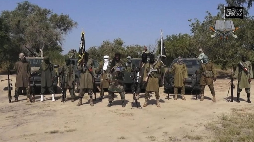 This file image taken from video released Oct. 31, 2014, by Boko Haram, shows Abubakar Shekau, center, the former leader of Nigeria's Islamic extremist group. Boko Haram now has a new leader who promises to end attacks on mosques and markets used by Muslims, according to an interview published Wednesday, Aug. 3, 2016 by the Islamic State.
