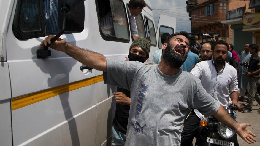 An unidentified relative of Riyaz Ahmad Shah, one among two civilians killed by government forces wails as an ambulance carrying his body arrives at his home in Srinagar, Indian controlled Kashmir, Wednesday, Aug. 3, 2016. Fresh protests flared in Indian-controlled Kashmir on Wednesday following the overnight killings of two civilians by government forces amid a nearly monthlong security lockdown and protest strikes. (AP Photo/Dar Yasin)