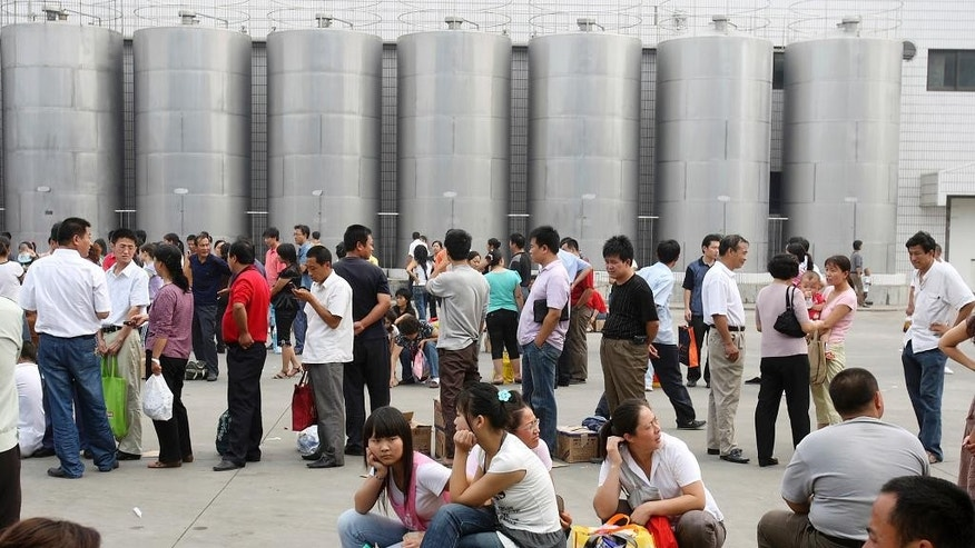 FILE - In this Sept. 18, 2008 file photo, Chinese consumers line up with tainted milk formula products to get a refund at a processing plant for Sanlu Group Co. whose milk formula products were found to contain banned substances in Shijiazhuang, northern China's Hebei province. Trials started this week of Chinese lawyers and legal rights activists who were detained in July last year and charged with subversion for their attempts to bring attention to abuses and demand government accountability. In 2008, Fengrui Law Firm represented victims in a contaminated infant formula scandal. The firm's work drew exactly the sort of attention that the government was hoping to avoid, further undermining public confidence in food safety and the leadership's commitment to candor and accountability. (AP Photo/Ng Han Guan, File)