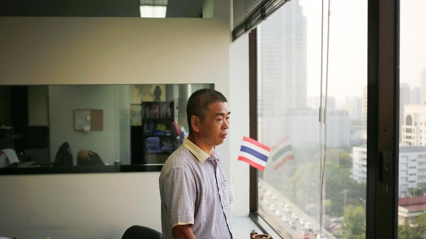 "FILE - In this March 11, 2016 file photo, Chinese asylum seeker Dong Junming, also a practitioner of the Falun Gong spiritual movement, which is banned in China looks out a window after an interview with the Associated Press in Bangkok, Thailand. Trials started this week of Chinese lawyers and legal rights activists who were detained in July last year and charged with subversion for their attempts to bring attention to abuses and demand government accountability. Fengrui Law Firm represented members of the Falun Gong meditation sect that the government has relentlessly suppressed since banning it as an ""evil cult"" in 1999. The firm has pursued numerous sensitive cases and represented outspoken critics of the ruling Communist Party. (AP Photo/Charles Dharapak, File)"