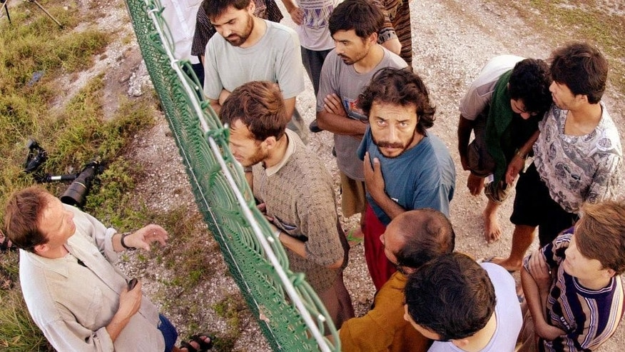 FILE - In this Sept. 19, 2001, file photo, refugees, right, gather on one side of a fence to talk with international journalists about their journey that brought them to the Island of Nauru. Human rights groups accused Australia on Wednesday, Aug. 3, 2016, of deliberately ignoring the abuse of asylum seekers being held at the remote Pacific island detention camp in a bid to deter future refugees from trying to reach the country by boat. (AP Photo/Rick Rycroft, File)