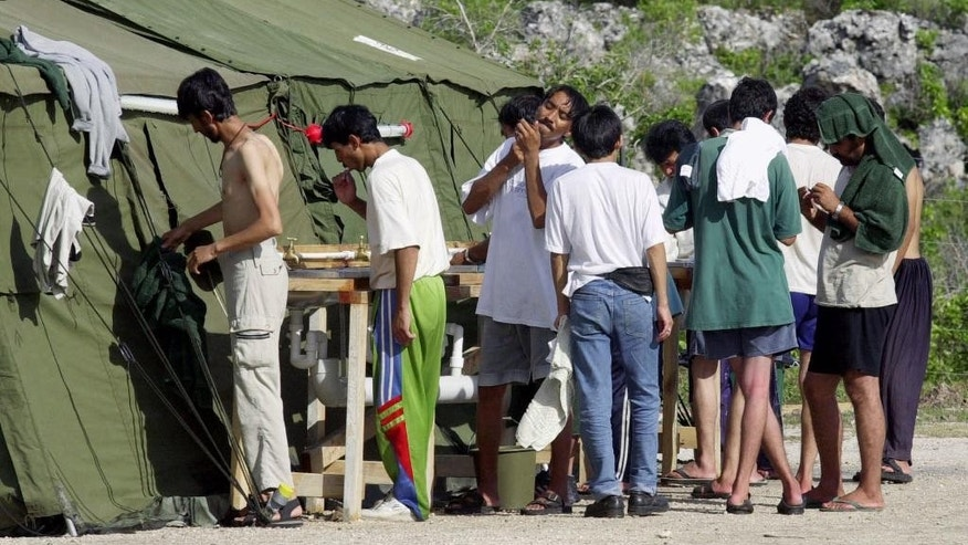 FILE - In this Sept. 21, 2001, file photo, men shave, brush their teeth and prepare for the day at a refugee camp on the Island of Nauru. Human rights groups accused Australia on Wednesday, Aug. 3, 2016, of deliberately ignoring the abuse of asylum seekers being held at the remote Pacific island detention camp in a bid to deter future refugees from trying to reach the country by boat. (AP Photo/Rick Rycroft, File)